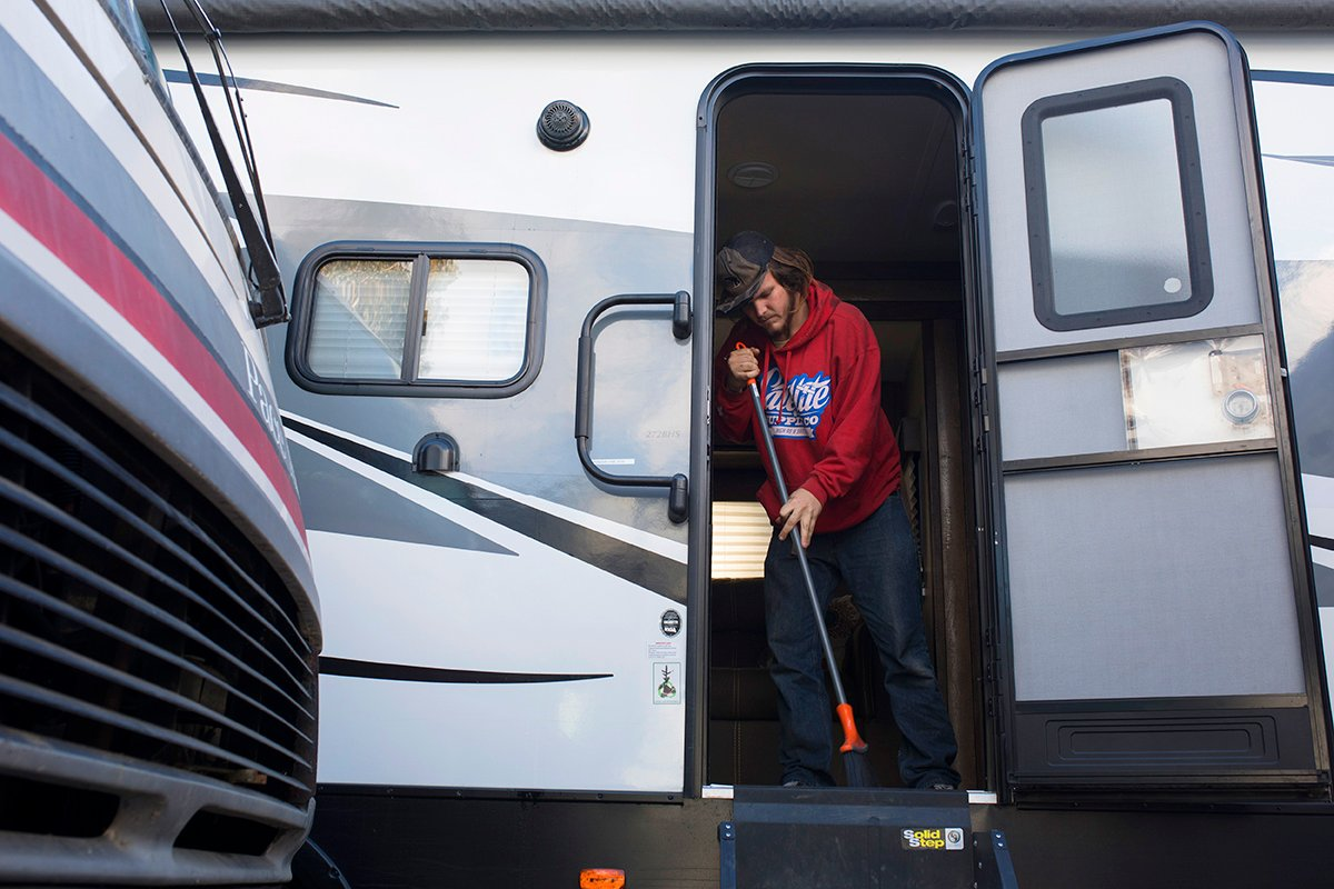 A young man sweeps out an RV