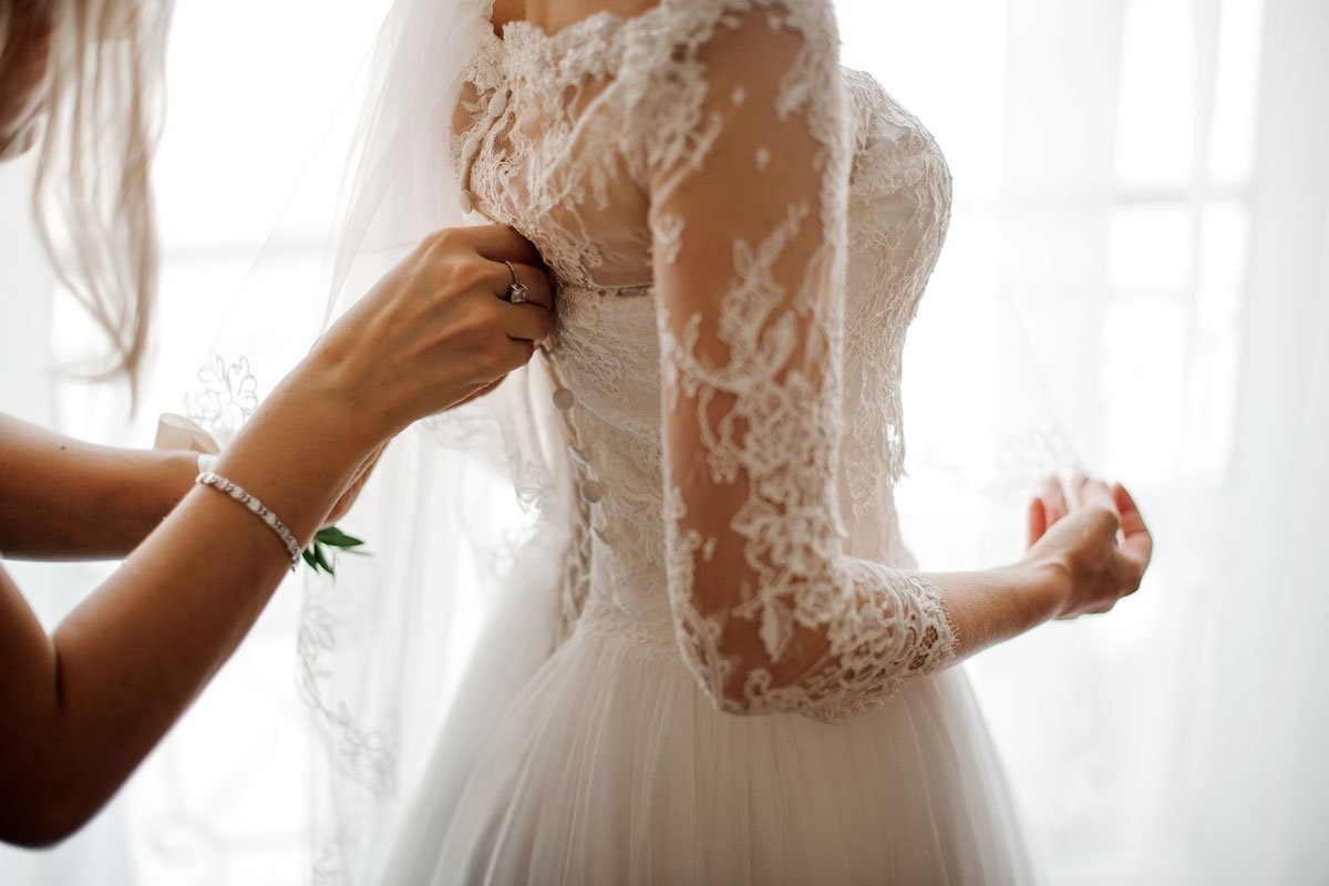A woman gets her wedding gown fastened in the back.